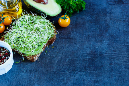 medicago: Tasty vegetarian sandwich with whole grain bread, alfalfa and guacamole on rustic wooden cutting board over dark vintage table, selective focus.