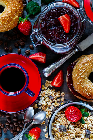 breakfast cup: Red cup of coffee, granola, fresh bagel with jam and strawberry for breakfast on rustic wooden background, top view.