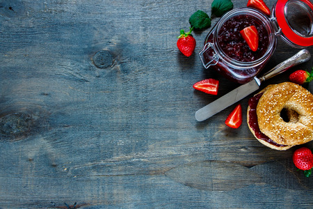 continental: Fresh bagel with jam and strawberry for breakfast on rustic wooden background with space for text, border, top view.