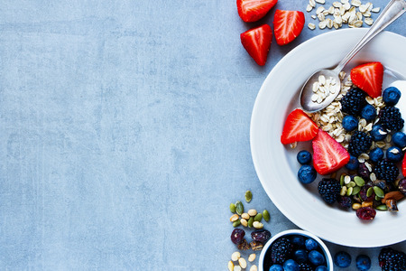 Close up of plate for breakfast with oat flakes, berries, yogurt and seeds on grey vintage background - Healthy food, Diet, Detox, Clean Eating or Vegetarian concept.