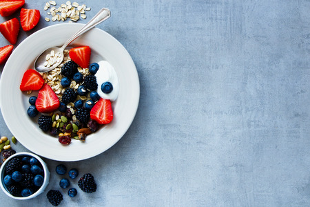 Top view of plate for breakfast with oat flakes, berries, yogurt and seeds on grey vintage background - Healthy food, Diet, Detox, Clean Eating or Vegetarian concept. Stock Photo