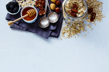 Tasty breakfast background with oat flakes, honey, berries and nuts on white vintage kitchen table, top view, place for text, border. Healthy food, Diet, Detox, Clean Eating or Vegetarian concept.