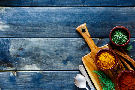 Cooking concept background with wooden cutting board and spices selection on vintage kitchen table, top view, place for text, border.