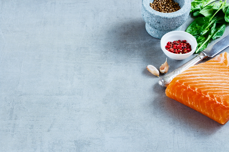 Portion of salmon fillet with fresh ingredients for tasty cooking on grey background, border, selective focus. Healthy or diet food concept. Stock Photo