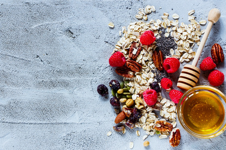 Top view of various ingredients for cooking healthy breakfast or smoothie (fresh berries, nuts, oat flakes, dried fruits, chia seeds and honey) over concrete textured background, place for text. Healthy food, Diet, Detox, Clean Eating or Vegetarian concep