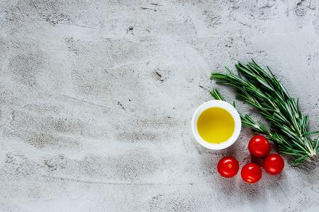 Organische groenten die ingrediënten met rozemarijn, olijfolie en tomaten koken over grijze concrete achtergrond, hoogste mening, plaats voor tekst, grens. Gezonde levensstijl of detox dieet voedsel concept. Stockfoto