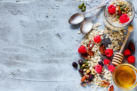 Colorful ingredients for cooking breakfast or smoothie (fresh berries, nuts, oat flakes, dried fruits, chia seeds and honey) over concrete textured background, place for text, top view. Healthy food, Diet, Detox, Clean Eating or Vegetarian concept.