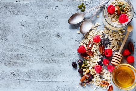 Kleurrijke ingrediënten voor het koken van ontbijt of smoothie (verse bessen, noten, havervlokken, gedroogd fruit, chiazaden en honing) over concrete geweven achtergrond, plaats voor tekst, hoogste mening. Gezond eten, dieet, detox, schoon eten of vegetarisch concept.