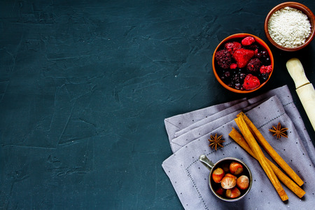 table top: Dark cooking table with ingredients for baking (whole flour, frozen berries, nuts and spices) over rustic background, place for text, top view.