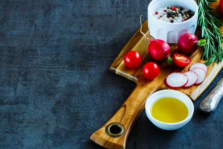 Close up of wooden cutting board with raw tasty vegetables, olive oil and spices on dark vintage background, selective focus, place for text. Healthy food. Vegetarian eating. Fresh harvest from the garden. Reklamní fotografie