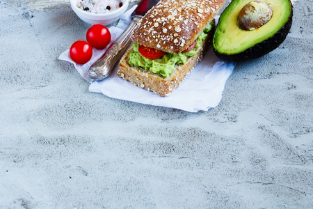 healthy snack: Delicious freshly made sandwich with avocado and tomatoes over concrete textured background, border, selective focus, space for text. Healthy snack concept. Stock Photo