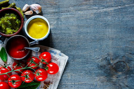 potherbs: Freshly made various sauces with fresh spices selection and textile napkin on dark textured kitchen table, top view. Rustic style background with space for text.