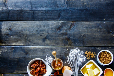 table top: Top view of wooden kitchen table with various ingredients for baking cake (white flour, butter, brown sugar, eggs, honey and nuts) over rustic background, copy space. Dark rural style.