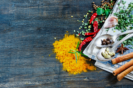 Close up of vintage wooden table with dry and fresh colorful herbs and spices selection (turmeric, paprika, rosemary, chives, pepper) on rustic background, selective focus, copy space. Dark rural style.