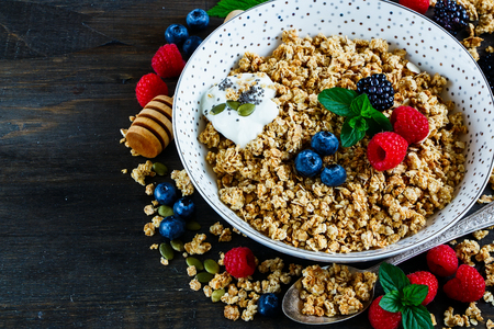 detoxing: Healthy breakfast granola, pumpkin and chia seeds, berries, banana, nuts over rustic wooden background with space for text. Stock Photo