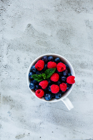 Ceramic cup with assortment berries blueberries and raspberries over concrete textured background. Top view composing. Stock Photo