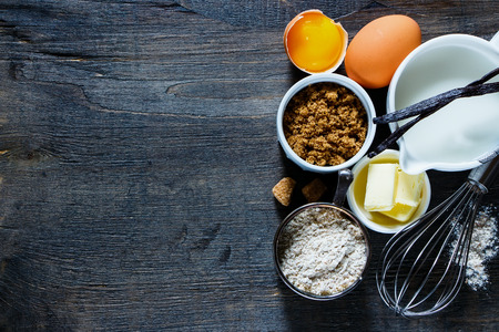 Tasty baking concept background with ingredients for making cake over vintage wooden board.Top view composing with space for text. Flat lay. Dark rustic style.