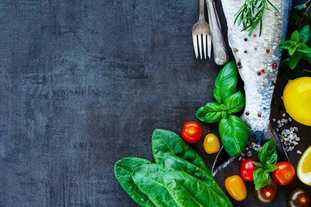 Bovenaanzicht van visgerechten koken achtergrond met ruimte voor tekst. Verse vis met Vaus ingrediënten op donkere uitstekende raad, voorbereiding. Plat. Gezond voedsel of dieet voeding concept.