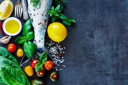 Close-up van visgerechten koken achtergrond met ruimte voor tekst. Verse vis met verschillende ingrediënten op donkere uitstekende raad, voorbereiding. Plat. Gezond voedsel of dieet voeding concept.