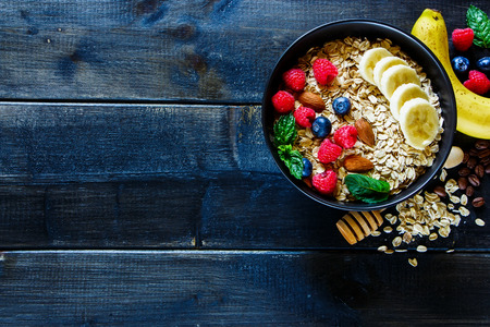 Food concept background with balanced breakfast composition on rustic wooden background.Oat flakes, fresh berries, nuts and banana in black bowl, border, top view. Healthy lifestyle and diet. Flat lay.