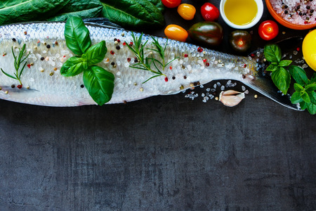 gilthead bream: Close up of healthy fish dishes cooking background with space for text. Raw fish with various ingredients on dark vintage board, preparation. Flat lay. Healthy food or diet nutrition concept. Stock Photo