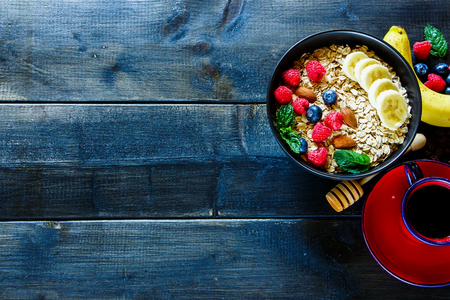 Close up of balanced breakfast composition with coffee cup and oat flakes, fresh berries, nuts, banana in black bowl on rustic wooden background, border, top view. Healthy lifestyle and diet food concept. Flat lay. Reklamní fotografie