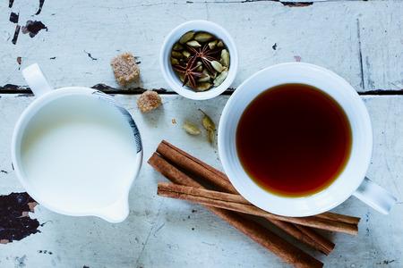 伝統的なインドのマサラ紅茶スパイス (シナモン、アニス、カルダモン、砂糖) 白いセラミック カップ、トップ ビューで古い木製の背景を持