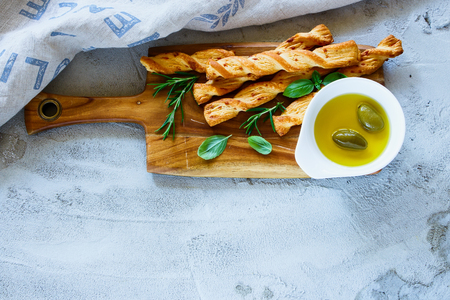 Top view of fresh baked grissini bread sticks on wooden cutting board with olive oil and herbs rosemary and basil over grey concrete textured background, copy space.
