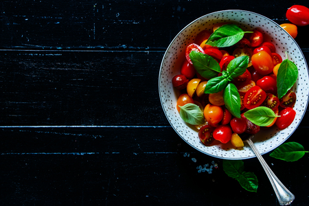 Kitchen table with bowl of healthy and fresh salad with tomatoes, olive oil and basil leaves on dark wooden vintage background, top view, copy space. Stok Fotoğraf