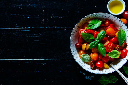 Top view of dark kitchen table with bowl of healthy and fresh salad with tomatoes, olive oil and basil leaves on wooden vintage background, copy space.