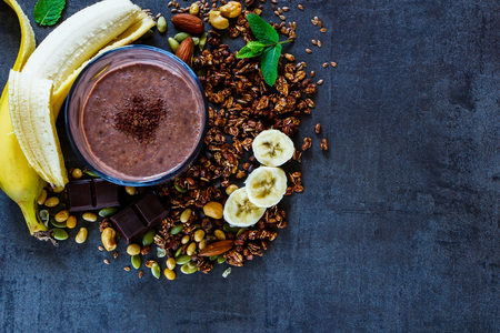 Delicious freshly made banana chocolate smoothie with homemade granola, nuts, seeds and mint on dark vintage backdrop with space for text, top view, banner. Healthy ingredients background. Stock Photo