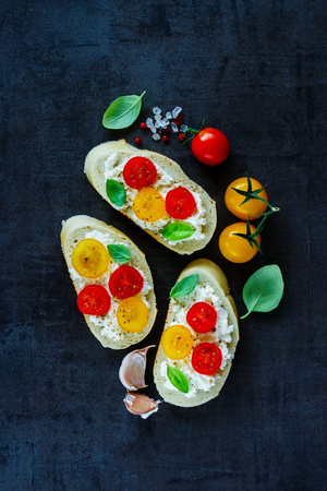 Dark cooking background with delicious tomato and basil bruschetta or sandwiches and ingredients over vintage table, top view, flat lay - Italian, Vegetarian or Healthy food concept