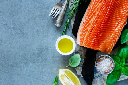 Close up of raw uncooked salmon fillet with aromatic herbs and spices on light grey background - healthy food, diet or cooking concept. Top view composition with dinner cooking ingredients.