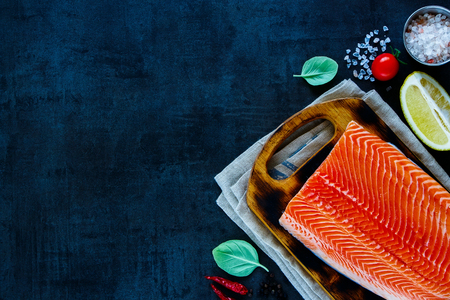 Portion of fresh uncooked salmon fillet with lemon, herbs and spices on little wooden cutting board over dark rustic background - healthy food, diet or cooking concept. Top view composition with dinner cooking ingredients.