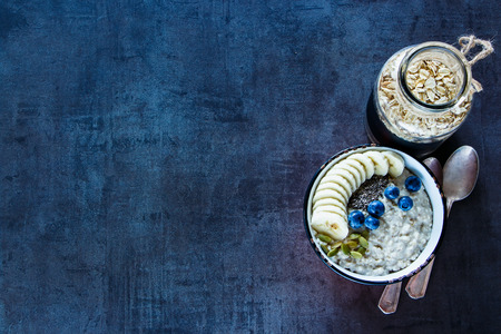 Healthy breakfast. Vintage ceramic bowl of home made oatmeal porridge, bananas, blueberries, pumpkin and chia seeds on dark grunge background. Rustic breakfast theme. Top view, space for text Stock Photo
