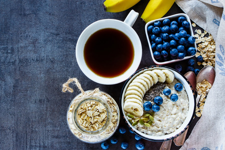 detoxing: Healthy breakfast. Freshly made oatmeal porridge, bananas, blueberries, pumpkin and chia seeds in vintage ceramic bowl with coffee on dark grunge background. Top view, space for text