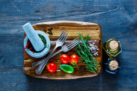 Top view of old chopping cutting board and fresh ingredients for healthy cooking on dark wooden background. Vegetarian food, health or cooking concept. Background layout with free text space.