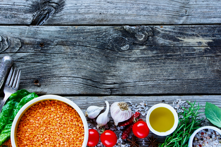 close up food: Top view of red lentil with variety of vegetables and ingredients for healthy cooking on rustic background, copy space, border. Vegan food or diet eating concept. Vegetarian eating concept.