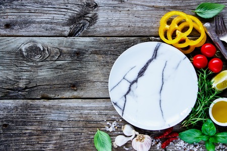 Top view of empty plate with raw various vegetables and seasoning cooking ingredients on grey rustic background, place for text. Vegan food, vegetarian and healthy eating concept.
