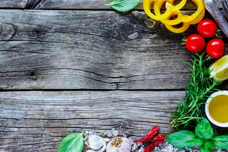 Food frame background with raw various vegetables and seasoning cooking ingredients on wooden rustic kitchen table, top view, place for text. Vegan food, vegetarian and healthy eating concept.