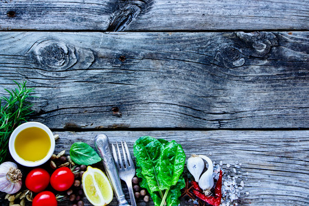 Close up of rustic wooden background with raw various vegetables and seasoning cooking ingredients on old kitchen table, top view, place for text. Vegan food, vegetarian and healthy eating concept. Stock Photo