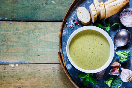 pepperbox: Green broccoli cream soup in white bowl with fresh baguette, basil and garlic on old rusty iron background over wooden rustic table. Top view. With copy space.