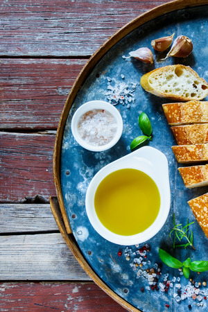 French fresh baguette, extra virgin Olive oil, spices and basil on old rusty iron background over rustic wooden table, top view, copy space.