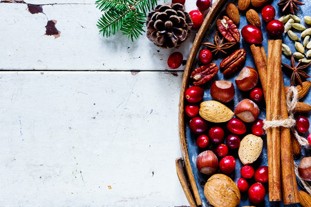 Natural Christmas Decor with nuts, cranberries and spices on old rusty iron background over white wooden rustic table, top view, copy space.