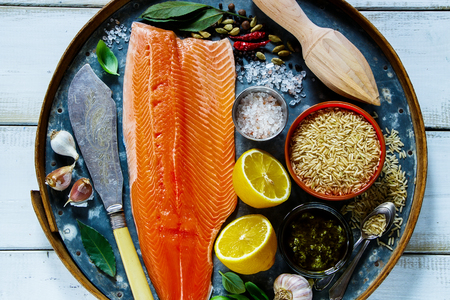 Salmon fillet and brown rice on old rusty iron background with fresh ingredients for tasty cooking over rustic wooden table, top view. Healthy or diet food concept.