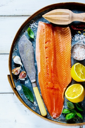 Top view of salmon fillet on old rusty iron background with fresh ingredients for tasty cooking  over rustic wooden table. Healthy or diet food concept. Stock Photo
