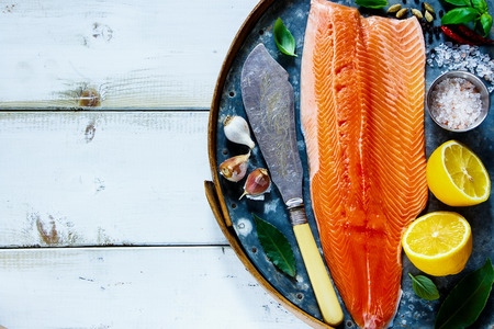 Salmon fillet on old rusty iron background with fresh ingredients for tasty cooking  over white wooden table, top view. Healthy or diet food concept.