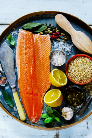 Raw salmon fillet and brown rice on old rusty iron background with fresh ingredients for tasty cooking over rustic wooden table, top view. Healthy or diet food concept.