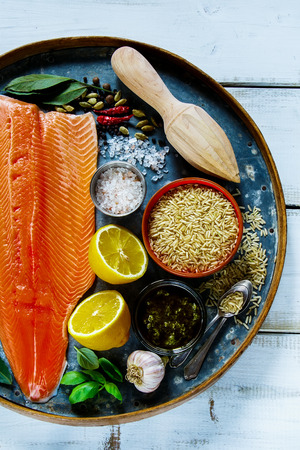 Fresh salmon fillet and brown rice on old rusty iron background with ingredients for tasty cooking over rustic wooden table, top view. Healthy or diet food concept. Stock Photo