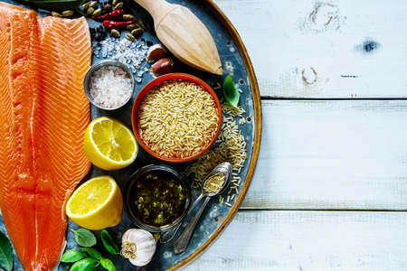 Close up of uncooked salmon fillet and brown rice on old rusty iron background with ingredients for tasty cooking over rustic wooden table, top view. Healthy or diet food concept. Stock Photo